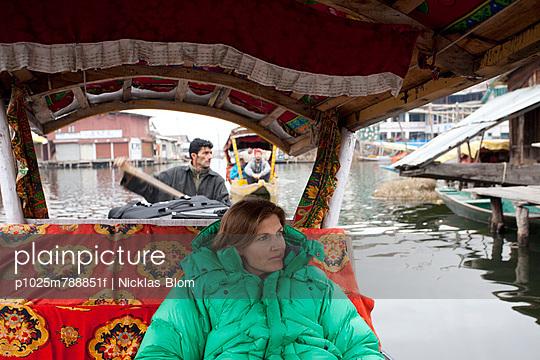 Woman in green jacket enjoying a boat ride in Asia