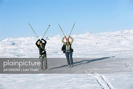 Tourists carrying ski poles