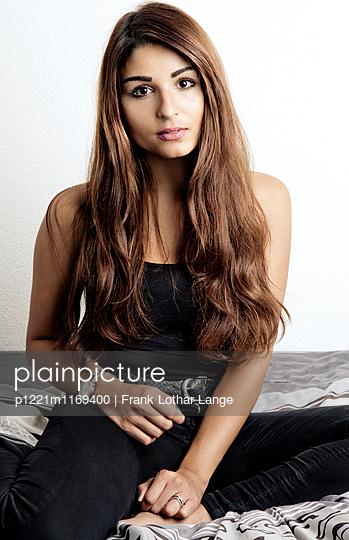 Junge Frau sitzt auf dem Bett - p1221m1169400 von Frank Lothar Lange