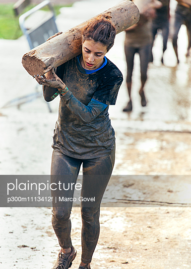 Participant in extreme obstacle race carrying tree trunk