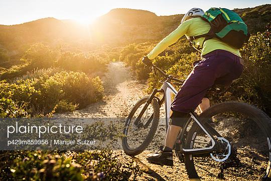 Young woman mountain biking on dirt track; Monterey; California; USA