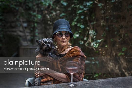 Fashionable senior woman with dog in garden
