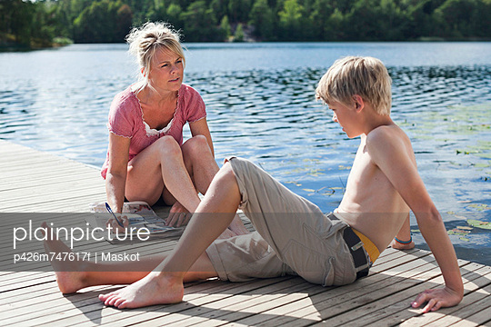 Mature woman writing on newspaper looking at son sitting on pier