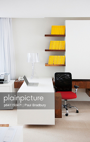 Laptop, desk and chair in modern office
