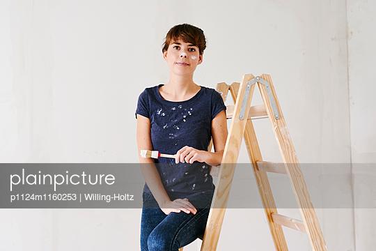 Frau mit Pinsel sitzt auf Leiter - p1124m1160253 von Willing-Holtz