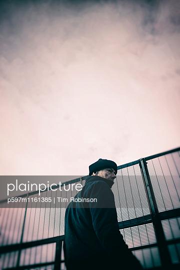 Seitenansicht eines Mannes vor einem Metallzaun - p597m1161385 von Tim Robinson