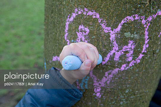 Child drawing heart on a tree trunk
