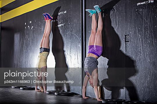 A pair of women doing handstands