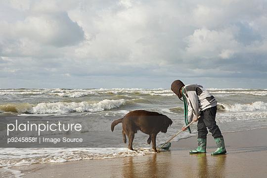 Boy by sea with dog
