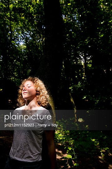 Mädchen lehnt an einem Baum im Wald - p1212m1152923 von harry + lidy