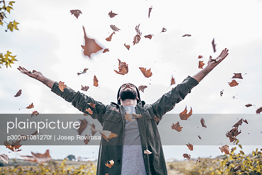 Young man throwing autumn leaves in the air