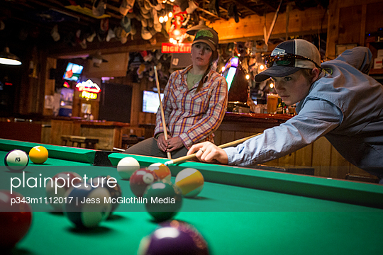 Two women play pool in a Montana bar.