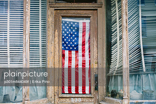 An American flag hanging in the door of a small business