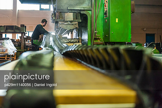 Man working in manufacturing plant on rubber production line