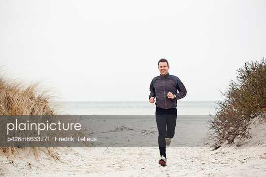 Portrait of a happy mid adult man jogging on beach against clear sky