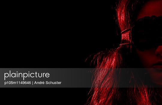 Junge Frau mit Augenmaske, rot beleuchtet - p105m1149646 von André Schuster