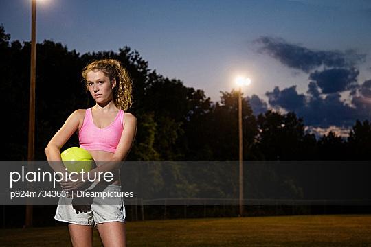Girl holding soccer ball at night