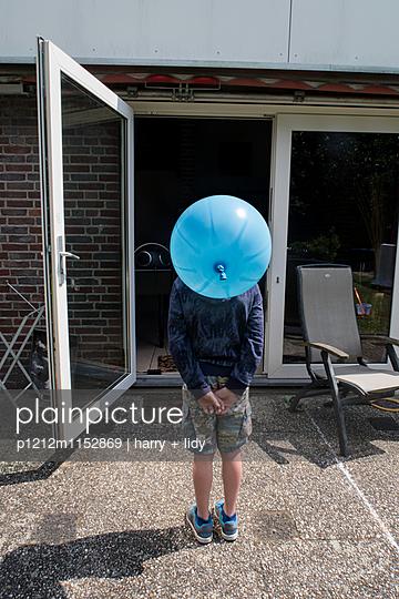 Junge mit Ballonkopf auf der Terasse - p1212m1152869 von harry + lidy
