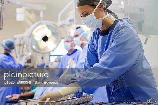 Nurse wearing scrubs preparing medical instruments in operating theater