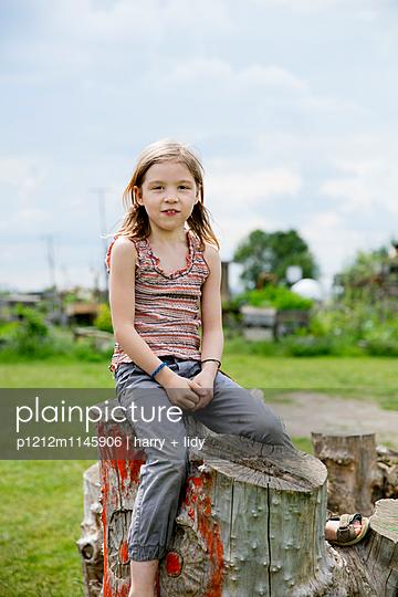 Mädchen sitzt auf Baumstumpf - p1212m1145906 von harry + lidy