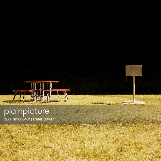 A picnic table and barbecue in a park at night, long exposure