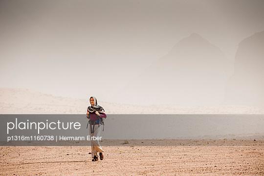 Frau wandert im diesigen Wadi Rum, Jordanien, Naher Osten - p1316m1160738 von Hermann Erber