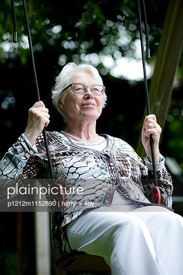 Weißhaarige Frau auf der Schaukel - p1212m1152890 von harry + lidy
