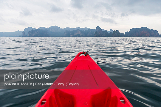 The tip of a sea kayak in the ocean while looking at a the coast of Krabi, Thailand.