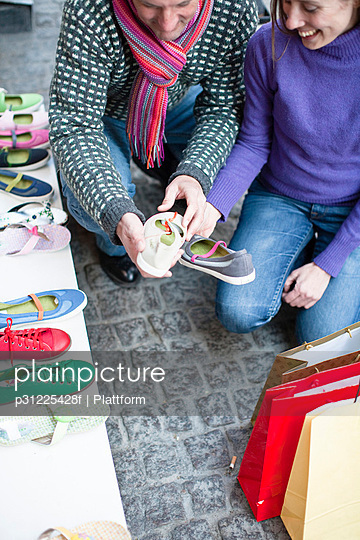 Couple observing shoes at outdoor market stall