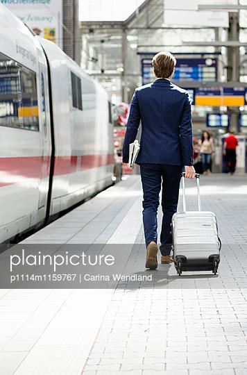 Geschäftsmann am Bahnsteig mit Rollkoffer - p1114m1159767 von Carina Wendland