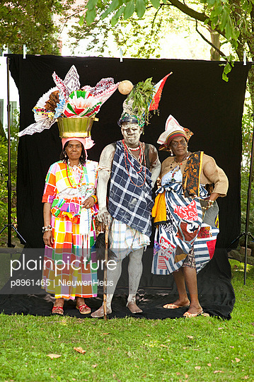 Three people of African descent dressed up in traditional cloth