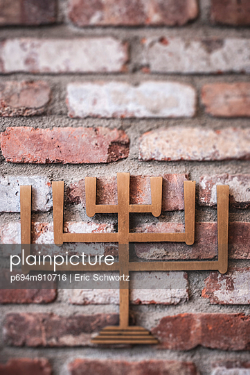 Metal Menorah Symbol on Brick Wall