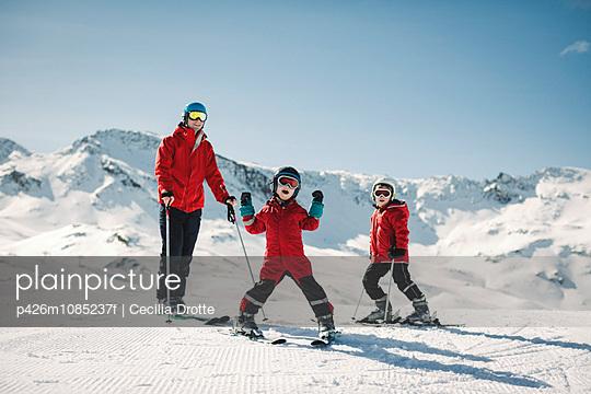 Portrait of family in ski-wear standing on snow against sky