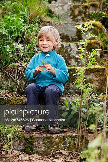 Boy holding flower and sitting on mossy steps