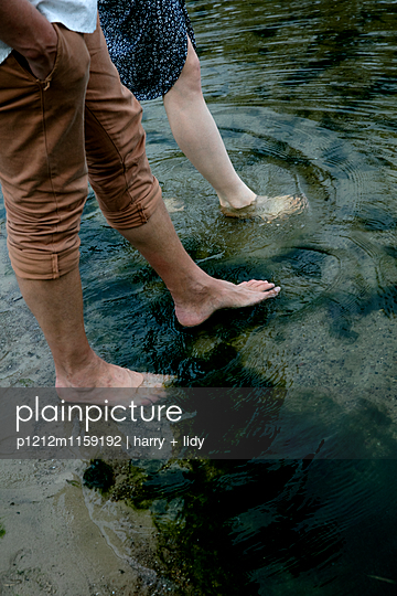 Unterkörper eines Jungen Paares im Wasser  - p1212m1159192 von harry + lidy