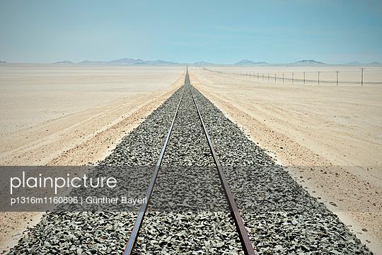 Gleise und Strommasten bis zum Horizont in der Wüste vor Lüderitz, Namibia, Afrika - p1316m1160896 von Günther Bayerl