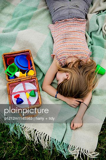 Mädchen schläft auf der Decke im Garten - Picknickkorb - p1212m1145983 von harry + lidy