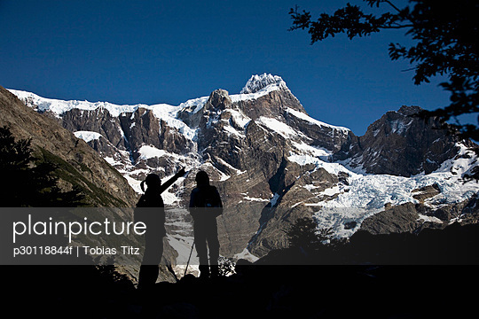 Two people in silhouette standing below snowy mountains, Torres del Paine National Park, Chile