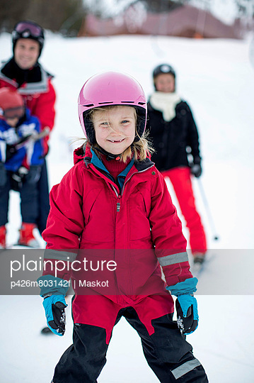 Portrait of girl in ski-wear with family in background