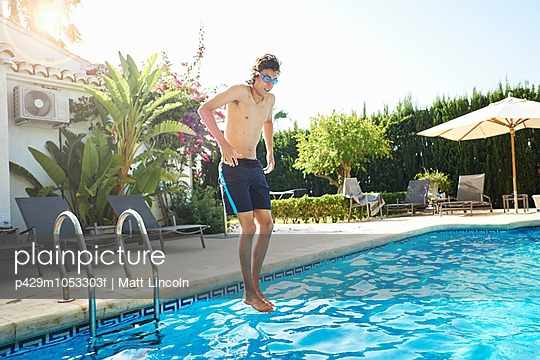 Young man wearing swimming goggles jumping into swimming pool