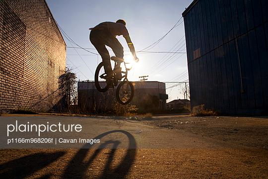 Silhouette of BMX biker doing bunny hop in alley