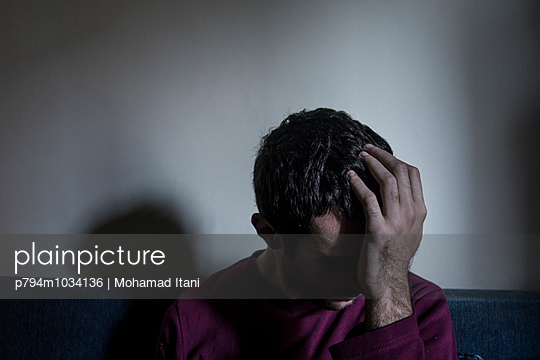 Depressed young man head in hands