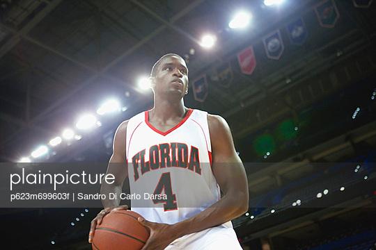 Basketball player holding basketball low angle view