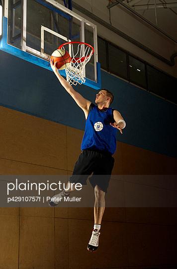 Basketball player jumping at hoop