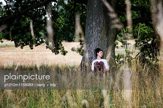 Junge Frau sitzt unter einem Baum - schläft - p1212m1159083 von harry + lidy