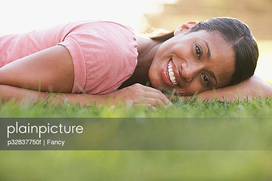 Happy Woman Lying Down in the Grass
