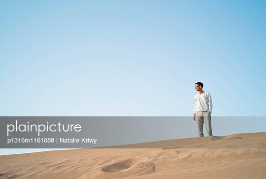 Mann auf einer Düne in der Wüste, Dubai, Vereinigte Arabische Emiraten - p1316m1161088 von Natalie Kriwy