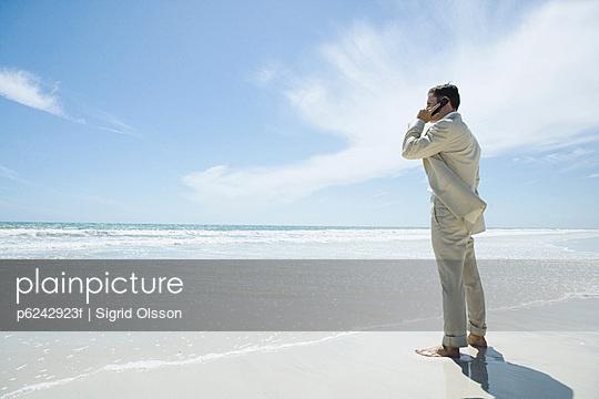 Businessman standing barefoot on beach