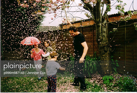 Family Playing Underneath Falling Blossom