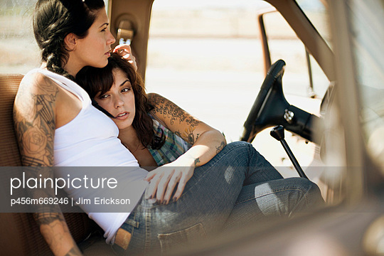 Two women cuddling on the driver\'s seat of a car